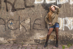 Young fashionable girl posing near the old wall. Stock Image