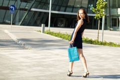 Young fashionable girl after shopping. Walking. Royalty Free Stock Images