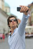 Young fashionable hipster Hispanic man with sunglasses taking a selfie. On the city street Stock Images