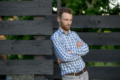 Young fashionable man against wooden fence Royalty Free Stock Photo