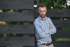 Young fashionable man against wooden fence Stock Image