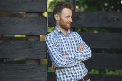 Young fashionable man against wooden fence Royalty Free Stock Photos