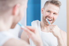 Young fashionable man brushing teeth Royalty Free Stock Photography