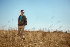 Young fashionable man with sunglasses and windbreaker standing outdoor. There is a  field as background Stock Images
