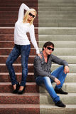Young fashionable man and woman on the steps Stock Images