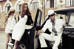 Young fashionable people at the retro car Royalty Free Stock Photo