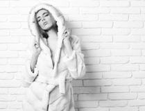 Young fashionable pretty woman or girl with beautiful long blonde hair in waist coat of white fur with hood and. Fashion makeup on brick wall studio background royalty free stock photos