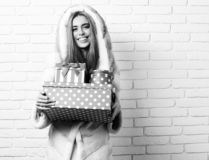 Young fashionable pretty woman or girl with long beautiful blonde hair in waist coat of white fur with hood and. Fashion makeup holding red big presents or royalty free stock photo