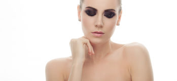 Young fashionable woman with bare shoulders and gorgeous dark smokey makeup touching her chin posing on white studio background Royalty Free Stock Image