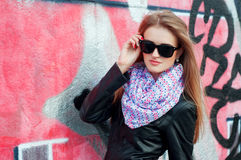 Young fashionable woman in black leather jacket and sunglasses Stock Photo