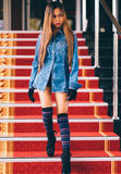 Young fashionable woman in blue jeans, and long striped knee socks walking down on stairs with the red carpet Stock Photography
