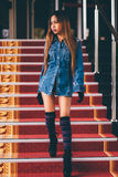Young fashionable woman in blue jeans, and long striped knee socks walking down on stairs with the red carpet Stock Photos