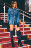 Young fashionable woman in blue jeans, and long striped knee socks walking down on stairs with the red carpet.  Royalty Free Stock Photography