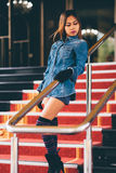 Young fashionable woman in blue jeans, and long striped knee socks walking down on stairs with the red carpet.  stock image