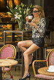 Young fashionable woman with a Cup of coffee in the cafeteria. Royalty Free Stock Photos