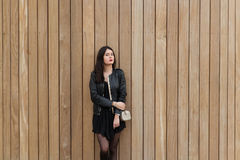 Young fashionable woman dressed in cool clothes dreaming about something while standing against wooden wall, Royalty Free Stock Images