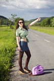 Young fashionable woman hitchhiking Royalty Free Stock Image