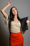 Young fashionable woman in a red skirt with black bag Stock Image