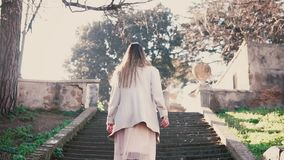 Young fashionable woman running up the stairs. Stylish girl walking in spring old town, bright sunlight in the morning. stock footage