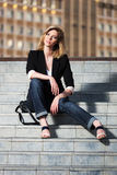 Young fashionable woman sitting on the steps Royalty Free Stock Photo
