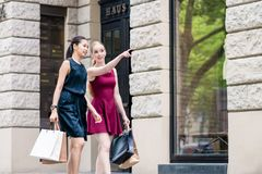 Young woman showing direction to her friend during shopping session. Young fashionable women showing direction to her friend during shopping session downtown in Stock Image