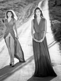 Young fashionable women waking on country side road Royalty Free Stock Image