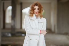 Young fashionably dressed red-haired girl with curly hair in a white coat posing, looking at the camera in an abandoned room royalty free stock photo