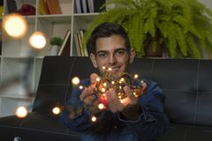 Young fashioned with christmas lights. At home stock photography