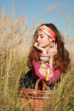 Young fashioned woman with a basket in field Royalty Free Stock Photos