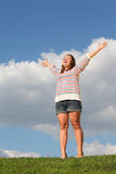 Young fat girl stands at grass, raises her hands Stock Images