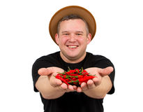 Young fat man with chili in his hands. Royalty Free Stock Photos