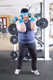 Young fat man doing a workout with barbells. Portrait of young fat man doing a workout with barbells while standing in the gym center Royalty Free Stock Photo