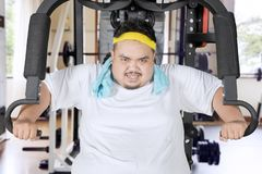 Young fat man exercising with a fitness machine royalty free stock photo