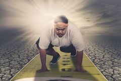 Young fat man kneeling above measuring tape stock image