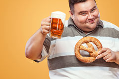 Young fat man at oktoberfest, drinking beer and eating pretzel on yellow background. Stock Photo