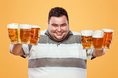 Young fat man at oktoberfest, drinking beer on yellow background. Royalty Free Stock Photo
