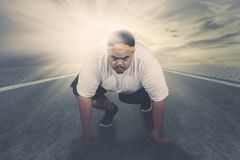Young fat man ready to run on the road stock images