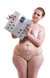 Young fat woman with bathroom scales Stock Images
