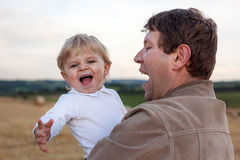 Young father and  adorable little son having fun on straw field Stock Photos