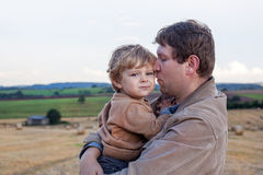 Young father and  adorable little son hugging on straw field Royalty Free Stock Image