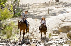 Young father as horse instructor of young teen daughter riding little pony wearing cowgirl hat Stock Photography