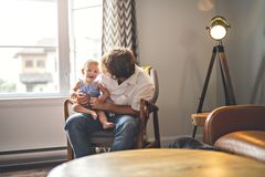 Young father with baby daughter on chair at home royalty free stock photo
