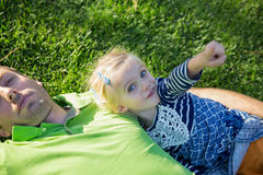 Young father with baby daughter lying on grass in a park Royalty Free Stock Photography