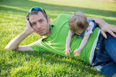 Young father with baby daughter lying on grass in a park stock images