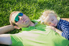Young father with baby daughter lying on grass in a park Stock Photos