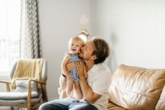 Young father with baby daughter on sofa at home royalty free stock images