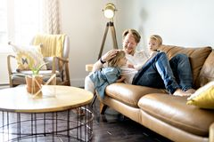 Young father with baby daughter and son on sofa at home royalty free stock images