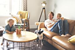 Young father with baby daughter and son on sofa at home stock photo