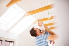 Young father with a baby son at home, having fun. Handsome young father with a baby son at home, having fun Stock Photo