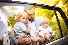 Young father with baby and toddler by the car. Man carrying baby girl and toddler boy. Shot through glass Royalty Free Stock Photos